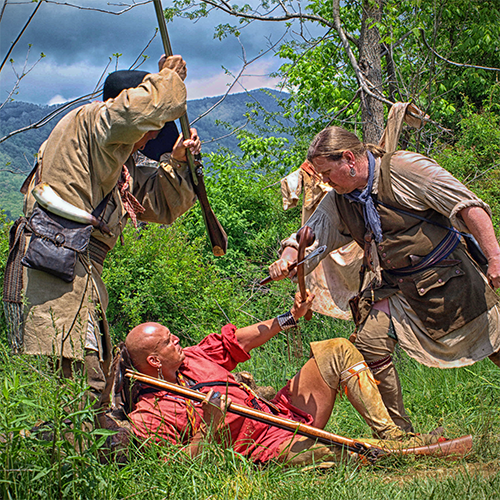 Two men dressed as English pioneer militiamen stand aggressively over an American Indian warrior who has been bested during the Raid at Martin's Station re-enactment at Wilderness Road State Park in Elydale, near Ewing, Lee County, Va.
