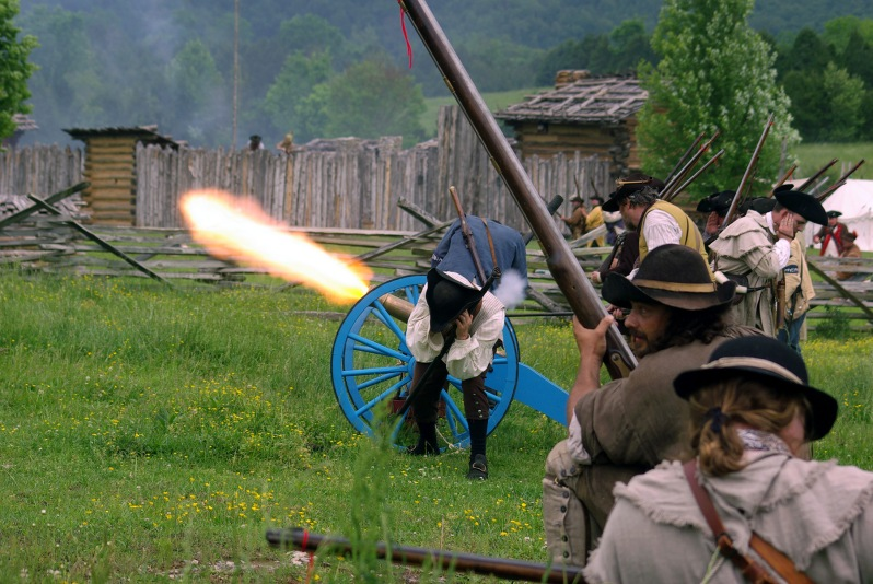 Re-enactors dressed in Colonial American milia uniforms and costumes fire and canon and wield long rifles and muskets during the Raid at Martin's Station at Wilderness Road State Park in Elydale, near Ewing, in Lee County, VA